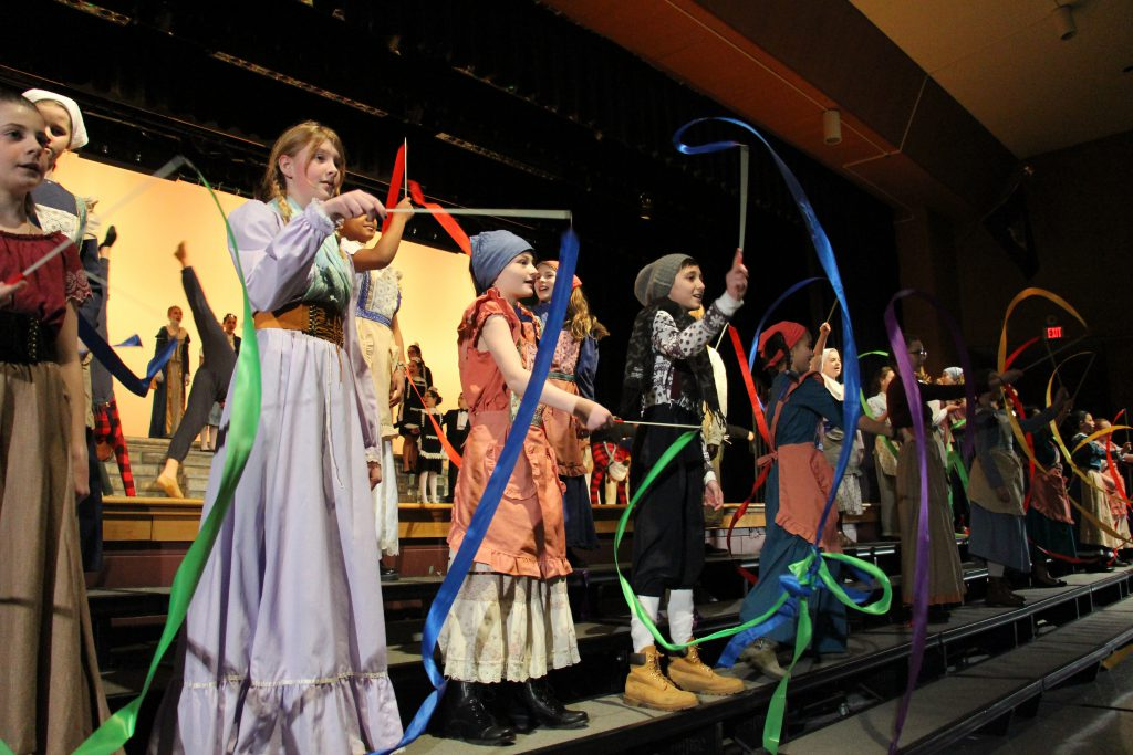 Middle school girls and boys dressed in costumes twirl brightly colored ribbons on sticks.