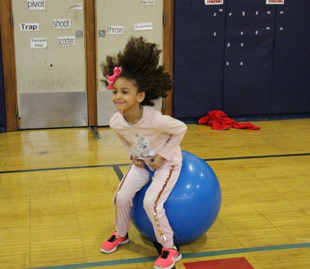 A girl in pink pants and shirt with a red bow in her hair bounces on a blue hippity-hoppity ball.