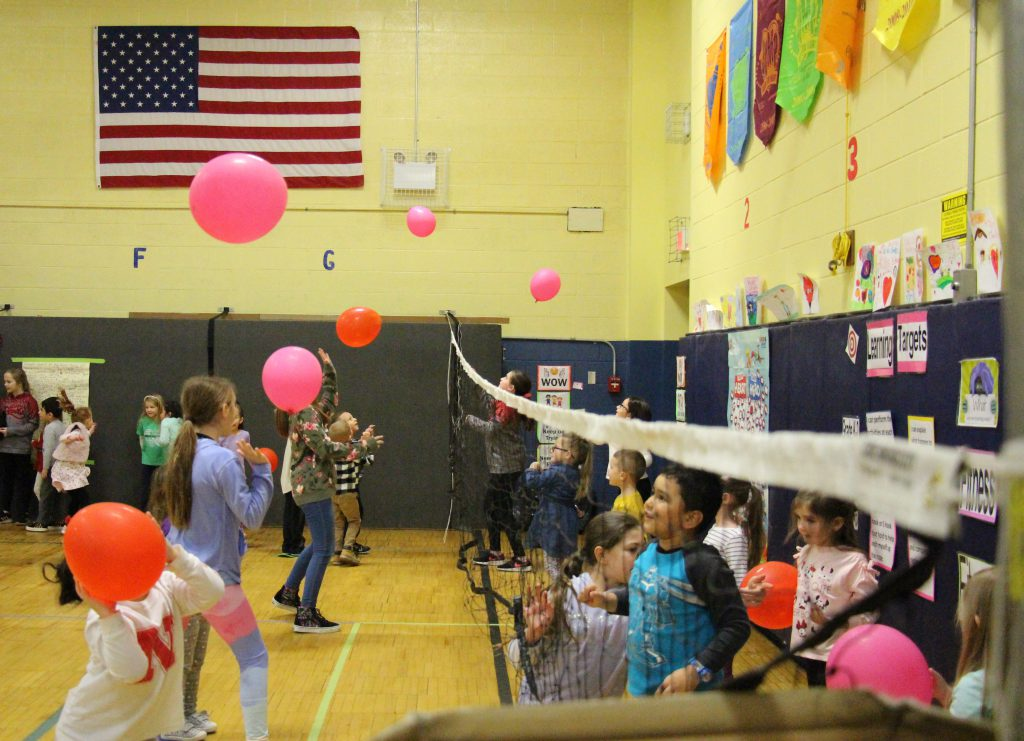 Balloons float in the air above a net as children play balloon volleyball.