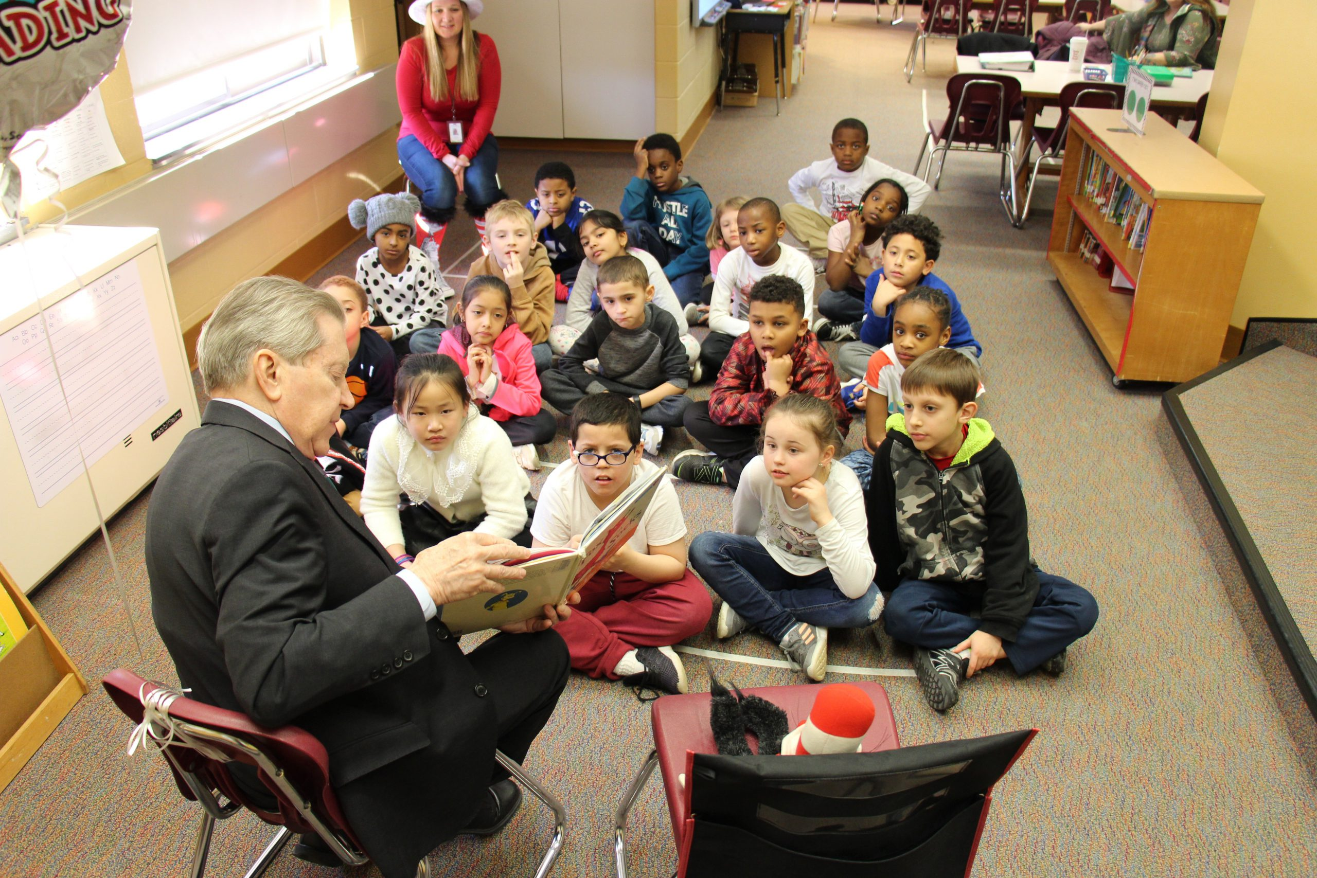 A class of second grade students sit on a rug in the library and listen as a man reads Fox in Sox to them.
