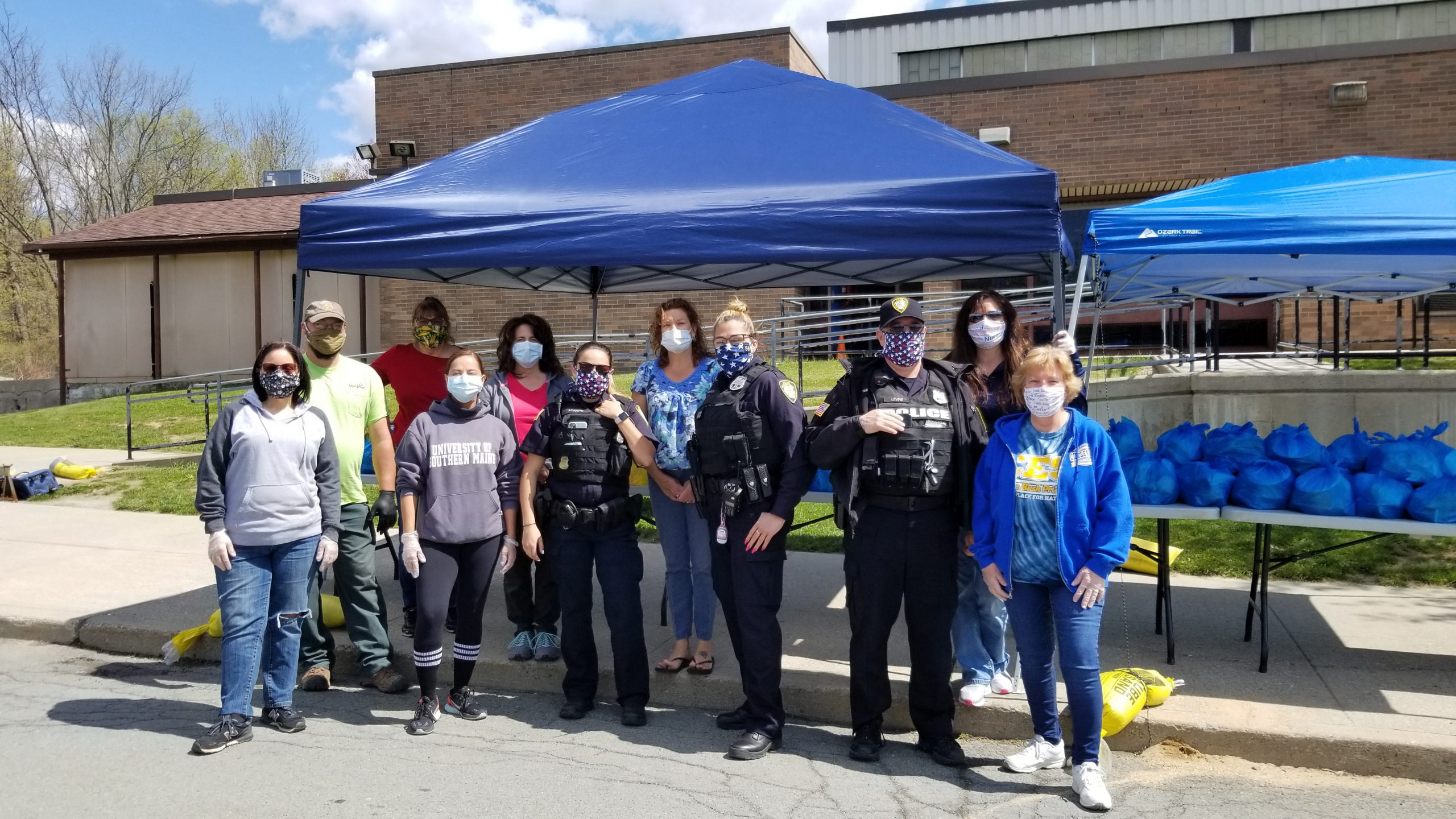a dozen people with masks on stand in front of a blue tent