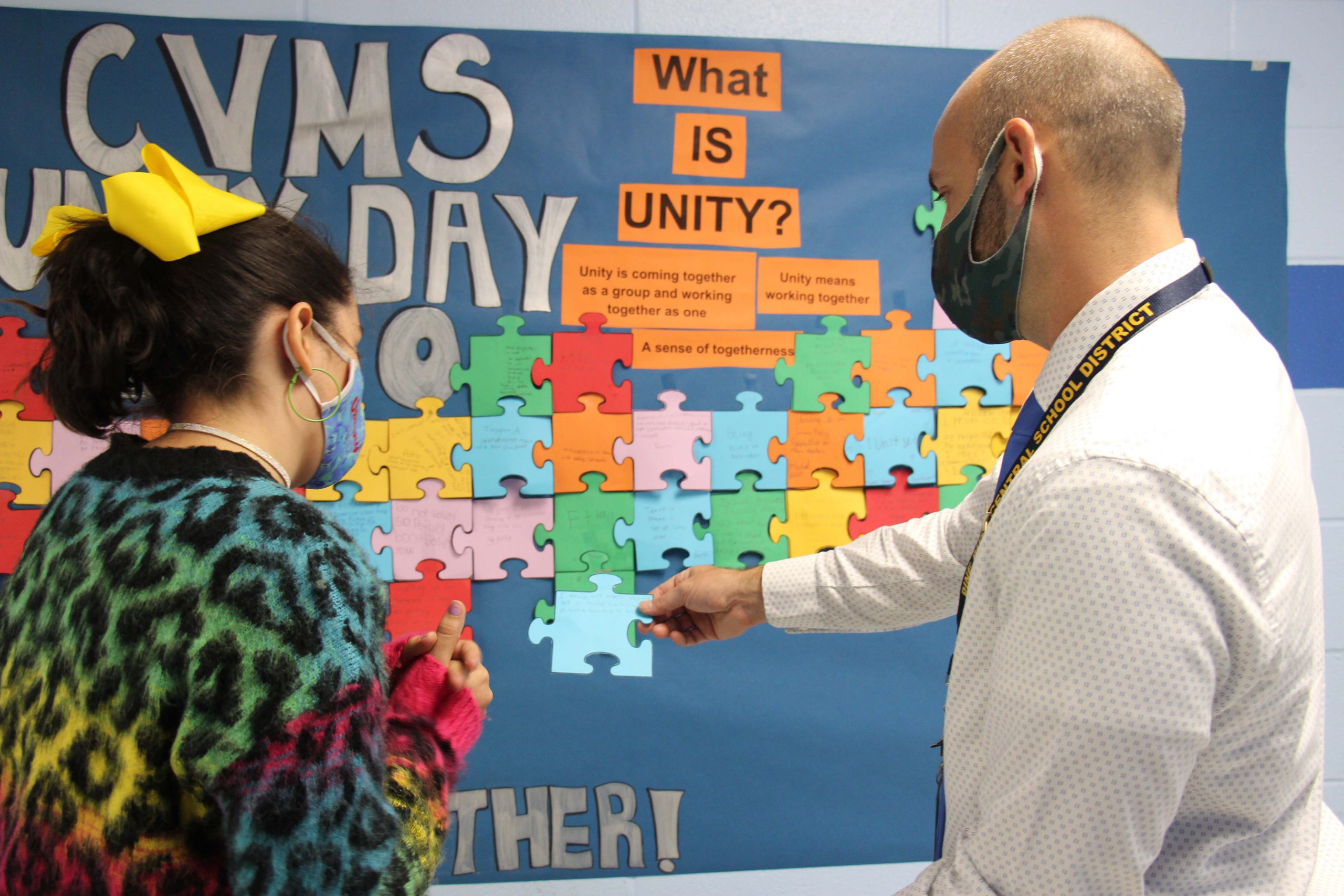 A man wearing a mask holds a blue puzzle piece out in front as a student , also wearing a mask, discusses what she wrote on it