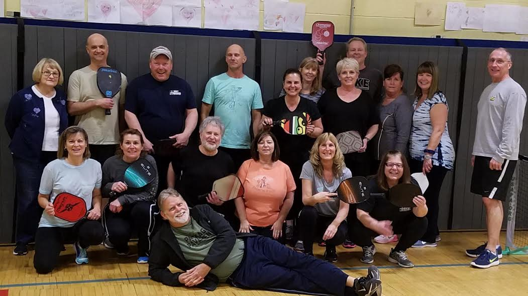 A group of 18 adults stand and kneel holding their pickleball paddles.