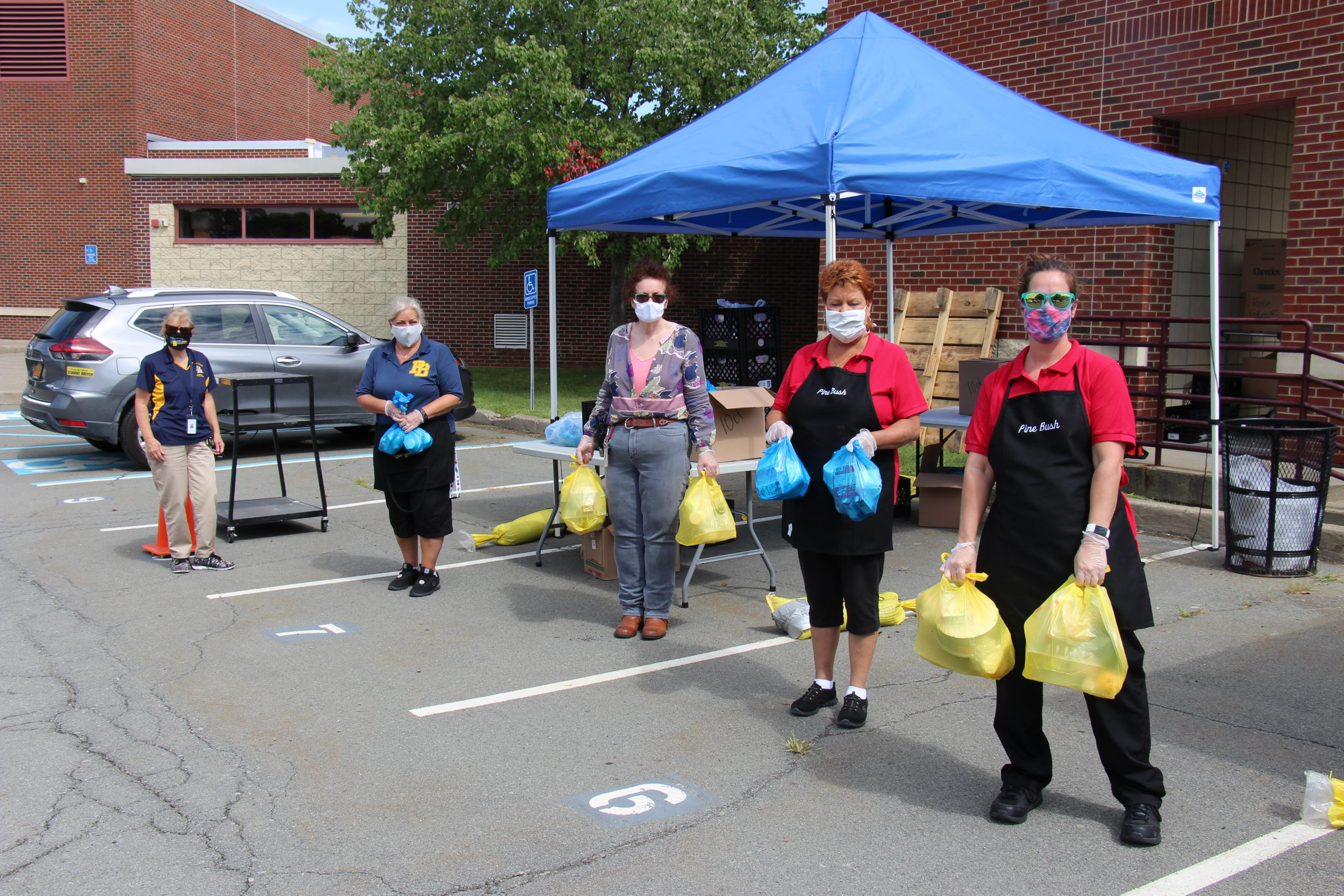 A line of five food services workers wearing aprons and masks hold plastic bags filled with food for students.