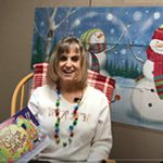 A woman sitting in a rocking chair wearing a Christmas sweater holds a book