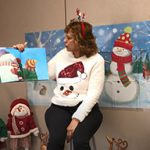 A woman wearing a snowman sweater and a red headband with snowmen on it holds up a book showing kids making snowmen.