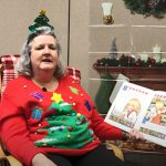 A woman in a red sweater with a large Christmas tree on it and a headband with a Christmas tree sits in a rocking chair reading a children's book