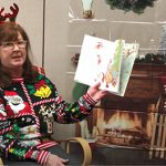 A woman with  festive Christmas sweater and a headband with antlers reads a book in front of a fireplace
