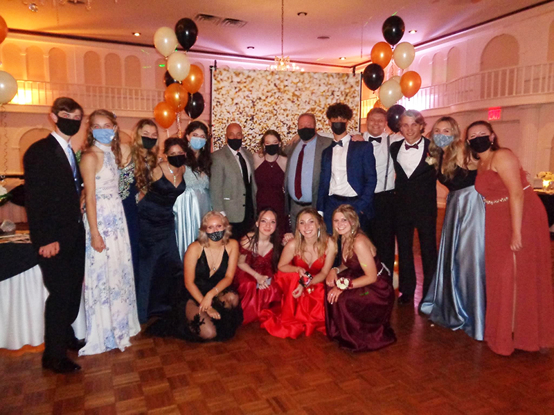 A large group of high school students dressed in tuxes and gowns.