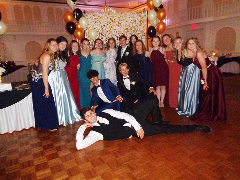 A large group of prom goers stand for the cmera. There is a young man laying on the floor in front of the group in his tuxedo.