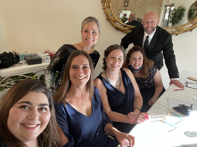 A group of six high school teachers, all dressed up, ,sit at a table at the prom.