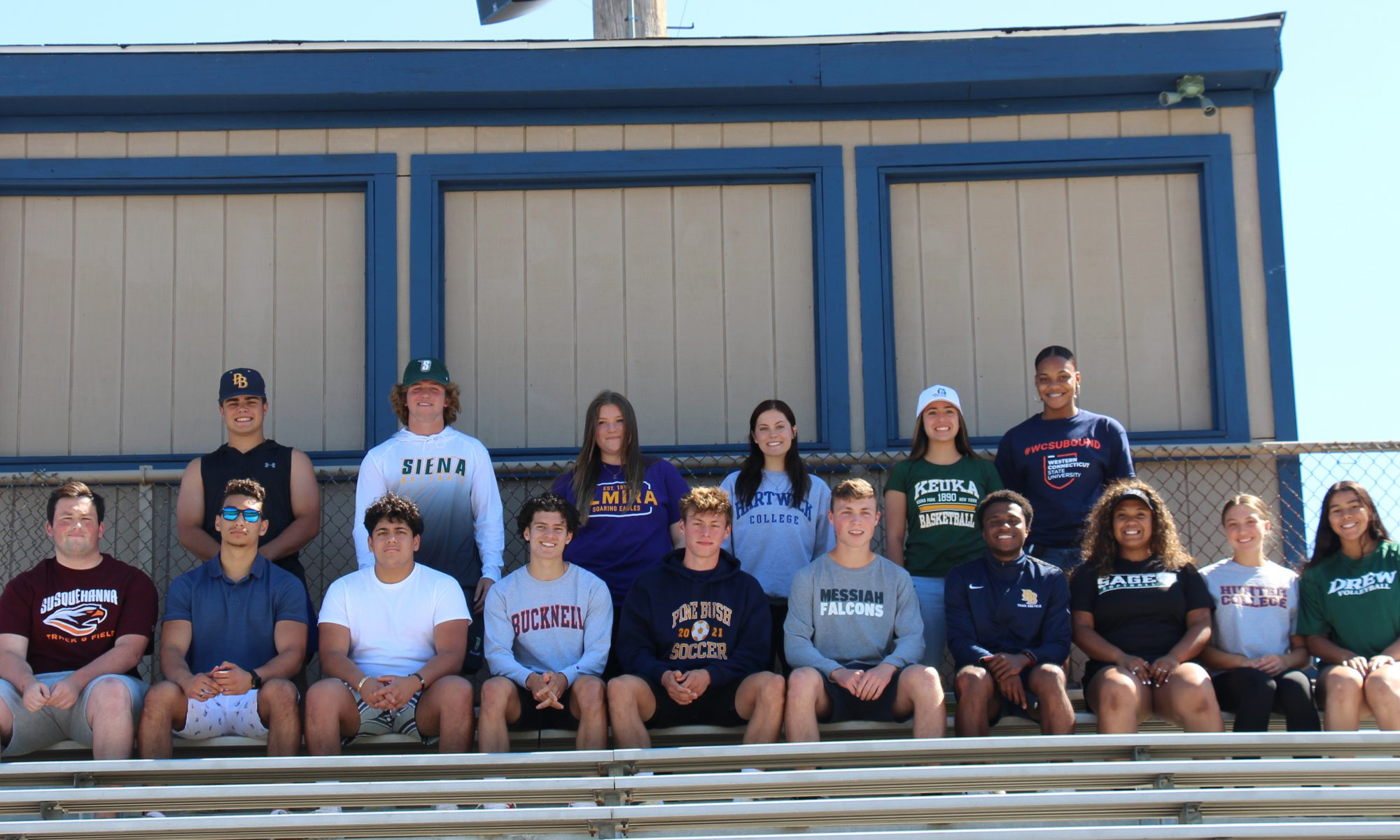 A group of athletes, most wearing their college shirts, sitting on the bleachers in front of the press box. There are two rows of kids, about 16 in total