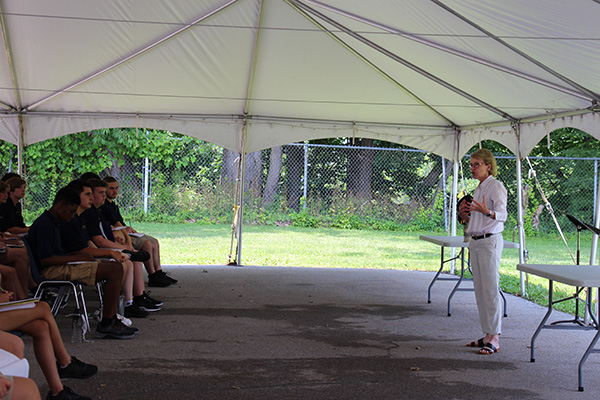 A woman with short blonde hair, wearing a white long sleeve shirt and tan pants stands in front of a group of high school students and talks.