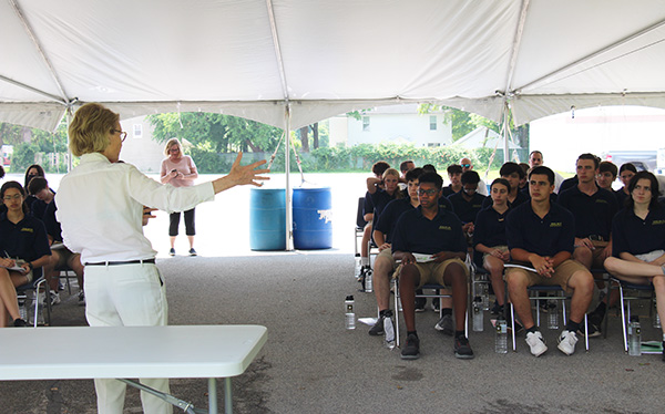 The back of a woman holding her arms out as she talks to a large group of high school students, sitting in two groups, under a large white tent. All of the students have navy blue shirts on and khaki shorts.