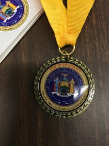 A medallion on a gold ribbon. The medalion is blue in the center with gold on the outside.
