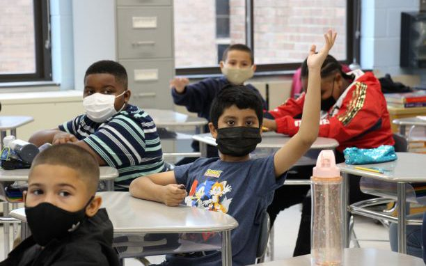 An elementary student raises his hand while sitting at a desk. He is wearing a navy blue tshirt with cartoon characters on it. There are several other students, all boys, sitting around him. Everyone has a mask on.